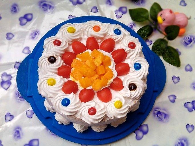 这是今年做的第二款生日蛋糕了,第一个奶油蛋糕是正月初五那天做给老爸的,因为他喜欢吃甜的东西所以蛋糕必须的呀,昨天去深圳表弟家玩,两个表弟和弟媳都喜欢吃蛋糕所以周六晚上我就把戚风烤好了,第二天早上才6点多就起来了:打发奶油、切水果、裱蛋糕。裱花蛋糕是我的弱项,又没有草莓和大家都喜欢的樱桃,就用了一样红艳艳的圣女果来装饰,加些芒果丁,最后又放上小朋友吃的巧克力豆,猛一看还是蛮好看的呢。做好放冰箱冷藏后叫大家起床然后换衣出来,一路上就放在车后排上,空调打的大大的生怕奶油化掉,到了又是第一时间塞进冰箱,保存的好好